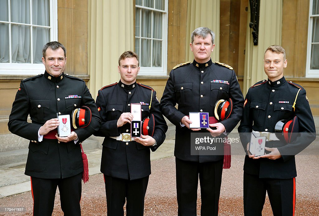 Maj Adam Wolfe MBE (Member of the British Empire), Lc Cpl Lawrence Kayser MC (Military Cross), Lt Col Michael Aston DSO (Distinguished Service Order), and Lc Cpl Lewis Treloar MBE (Member of the British Empire) from the Royal Anglian Regiment, after having their Medals presented to them by Queen Elizabeth II, at the Investiture ceremony at Buckingham Palace on June 13, 2013 in London, England.