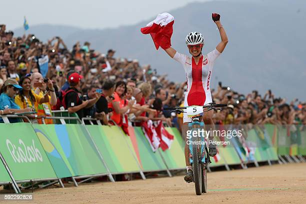 Maja Wloszczowska of Poland celebrates finishing second during the Women's CrossCountry Mountain Bike Race on Day 15 of the Rio 2016 Olympic Games at...