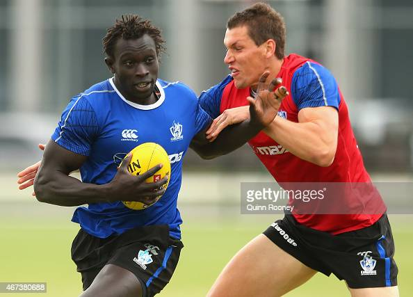 Majak Daw of the Kangaroos is tackled by Daniel Currie during a North Melbourne Kangaroos AFL training session at Arden Street Oval on March 24 2015...