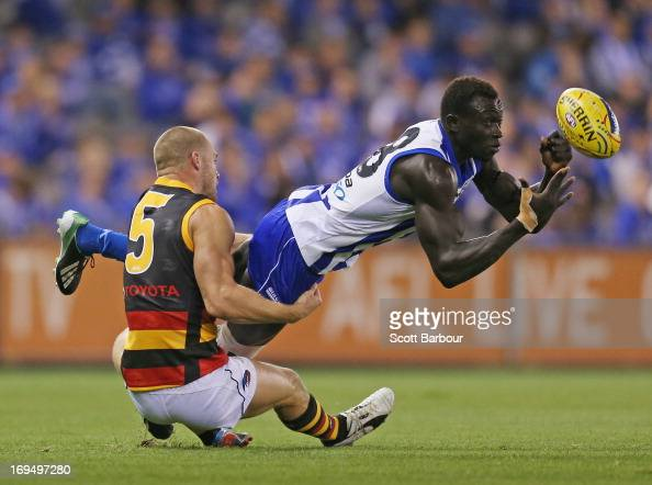 Majak Daw of the Kangaroos is tackled by Scott Thompson of the Crows during the round nine AFL match between the North Melbourne Kangaroos and the...