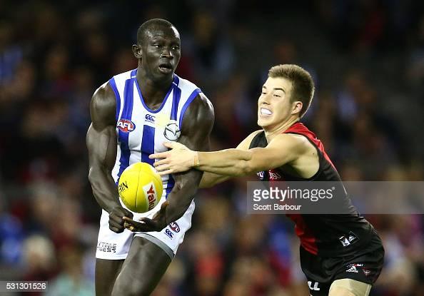 Majak Daw of the Kangaroos is tackled by Zach Merrett of the Bombers during the round eight AFL match between the Essendon Bombers and the North...