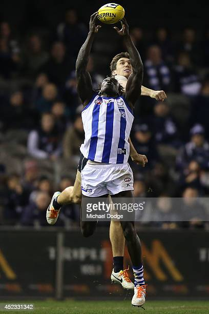 Majak Daw of the Kangaroos marks the ball against Michael Jamison of the Blues during the round 18 AFL match between the Carlton Blues and the North...