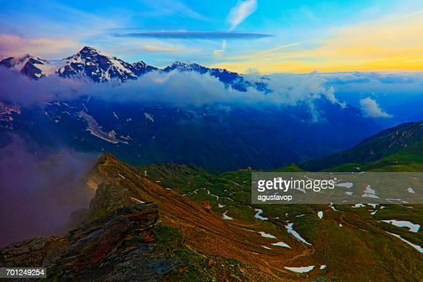 majestätische Hohe Tauern schneebedeckten österreichischen Gebirge bei Sonnenaufgang - Tirol Alpen dramatische Wolkengebilde Himmel und Landschaft und Großglockner-massiv
