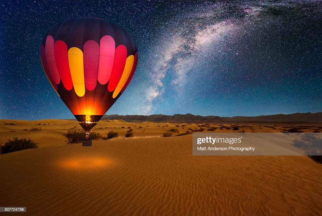 A majestic hot air balloon soars under the stars of the Milky Way, over the desert - Mesquite Dunes of Death Valley National Park. Moonlight provides luminosity showing the patterns and shapes of the desert landscape. : Stock Photo