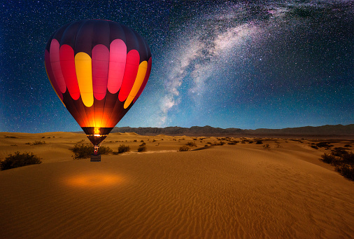 A majestic hot air balloon soars under the stars of the Milky Way, over the desert - Mesquite Dunes of Death Valley National Park. Moonlight provides luminosity showing the patterns and shapes of the desert landscape.