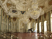Majestic large decorated piano concert hall. With golden decorations, sculptures, frescos and chandeliers.