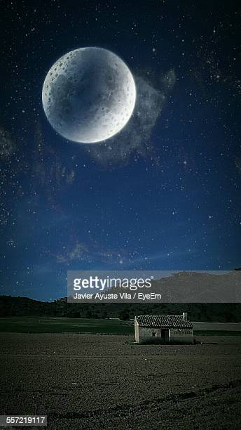 Majestic Moon Over House On Grassy Field