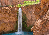 Mooney Falls plunges into a deep blue-green pool surrounded by red travertine cliffs on the Havasupai Indian Reservation in the Grand Canyon.