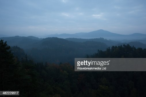 Trees and mountain range against cloudscape : Stock Photo
