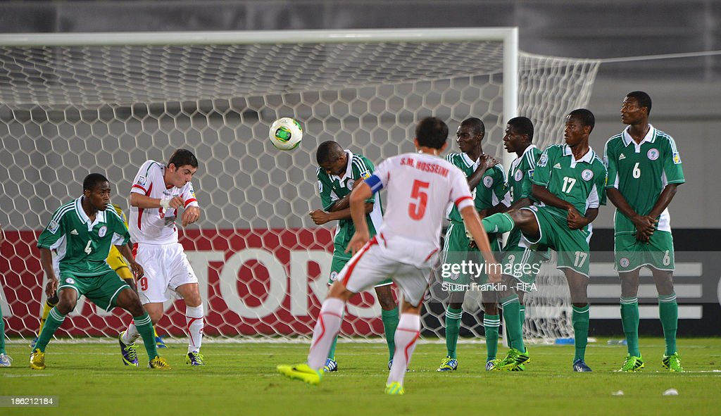 Majid Hosseini of Iran takes a free kick against a wall of Nigerian players during the round of 16 match between Nigeria and Iran at Khalifa Bin Zayed Stadium on October 29, 2013 in Al Ain, United Arab Emirates.