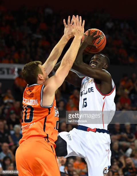 Majok Deng of the 36ers attempts a jump shot over Mitch McCarron of the Taipans during the round four NBL match between the Cairns Taipans and the...