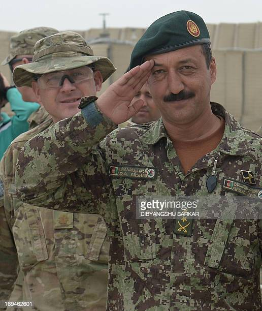 Major Albert Goetz of the US 10th Mountain Division looks on as Lieutenand Colonel Mohammad Arshad of the Afghan National Army salutes prior to their...