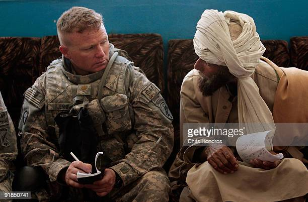 Major Christian Jenni of Ocean City New Jersey with the 405th Civil Affairs of the US Army listens to a local man as he airs a grievance during a...
