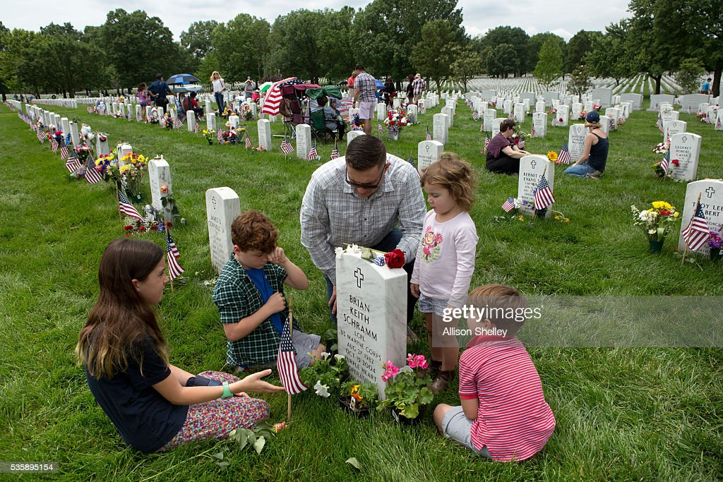Major Clint Kappel and his children, left to right, Reeder, 10, Hayes, 8, Amelia, 3, and Weiler, 5, pay respects to Brian Keith Schramm, in Section 60, the burial ground for military personnel killed since 2001, at Arlington National Cemetery on May 30, 2016 in Arlington, Virginia. Happel was Schramm's platoon commander during Operation Iraqi Freedom when the 22-year-old Marine Lance Corporal was killed by an artillery round in 2004. 'He was the sweetest guy you will ever meet,' says Kappel.
