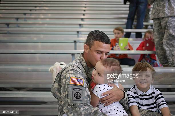 Major Dave Armeson of the US Army's 101st Airborne Division kisses his daughter Adelyn Armeson during a homecoming ceremony at Campbell Army Airfield...