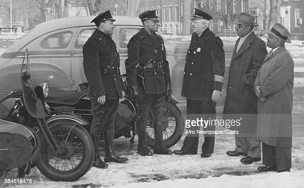 Major Edward Kelly of the Washington DC police speaks with two new AfricanAmerican patrolmen as Edward Harris and William A Powell look on Washington...