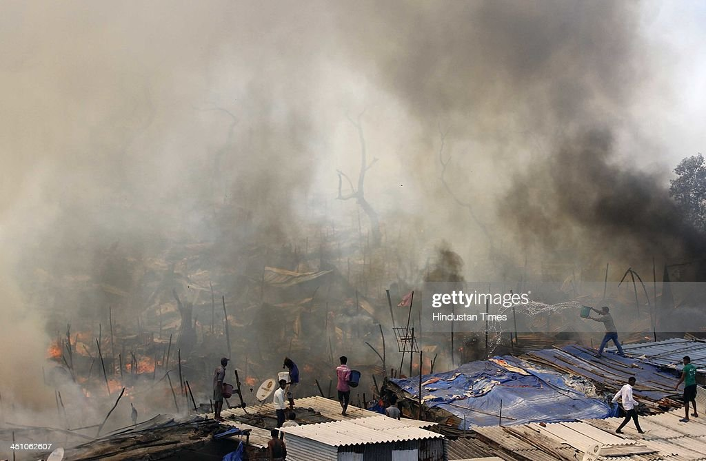 A major fire broke out at a construction site of a tightly-packed slum in Mumbai, destroying dozens of shanties as residents desperately tried to douse the flames at Ambedkar Nagar slum, Cuffe Parade on November 21, 2013 in Mumbai, India. Several huts were gutted in a fire that broke out in the settlement. About 10 fire engines and eight water tankers have been rushed to the spot to douse the flames.