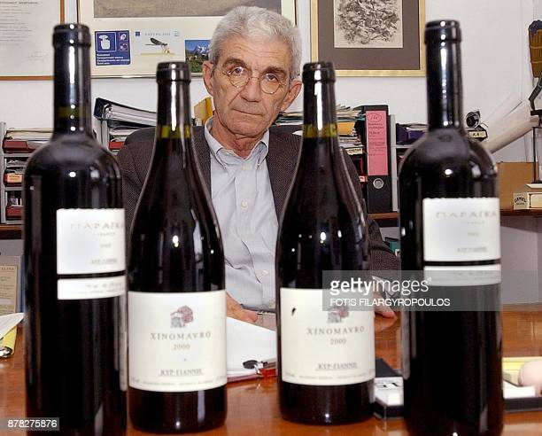 Major Greek winemaker Yiannis Boutaris is seen behind his ownbrand winebottles in his office in Athens Greece 16 November 2004 Boutaris has publicly...
