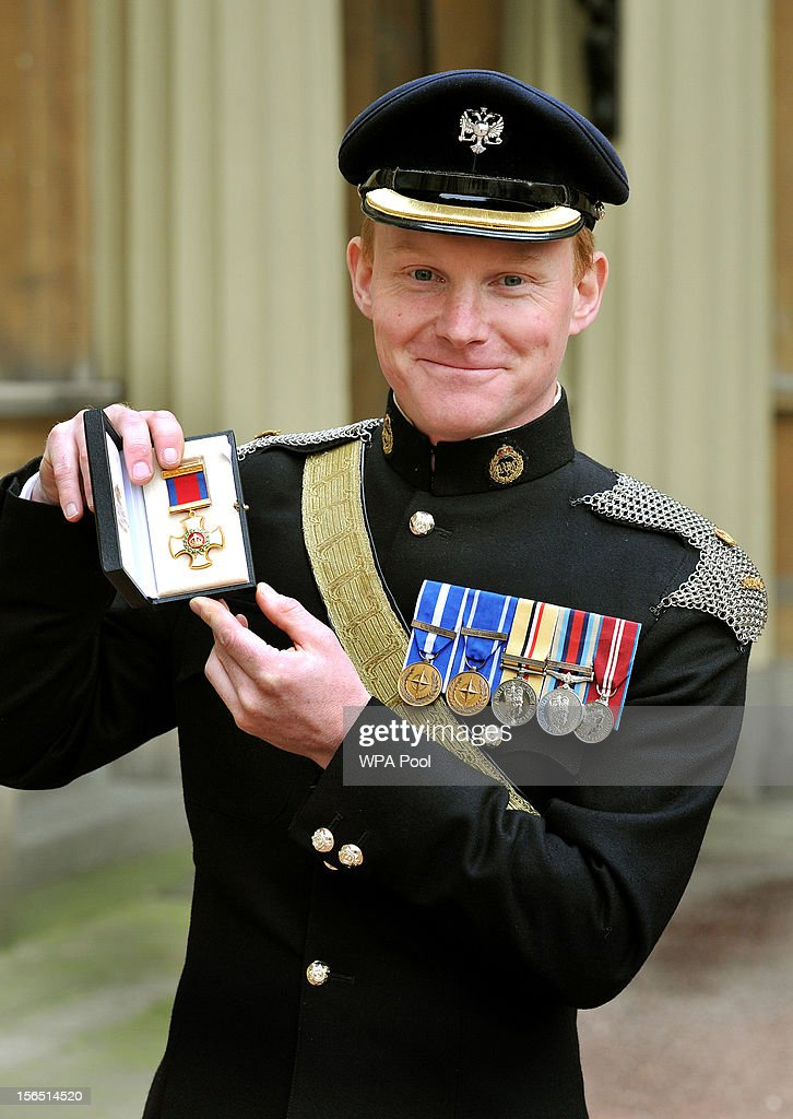 Major Justin Stenhouse of the Queen's Dragoon Guards proudly holds his Distinguished Service Order medal, after it was presented to him by Queen Elizabeth II at the Investiture ceremony at Buckingham Palace on November 16, 2012 in London, England.