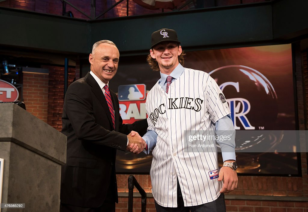 Major League Baseball Commissioner Robert D Manfred Jr shakes hands with Brendan Rodgers the third pick the 2015 Major League Baseball FirstYear...