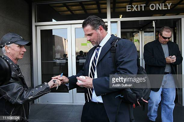 Major League Baseball player Jason Giambi signs an autograph as he and his brother Jeremy Giambi leave federal court after testifying during Barry...
