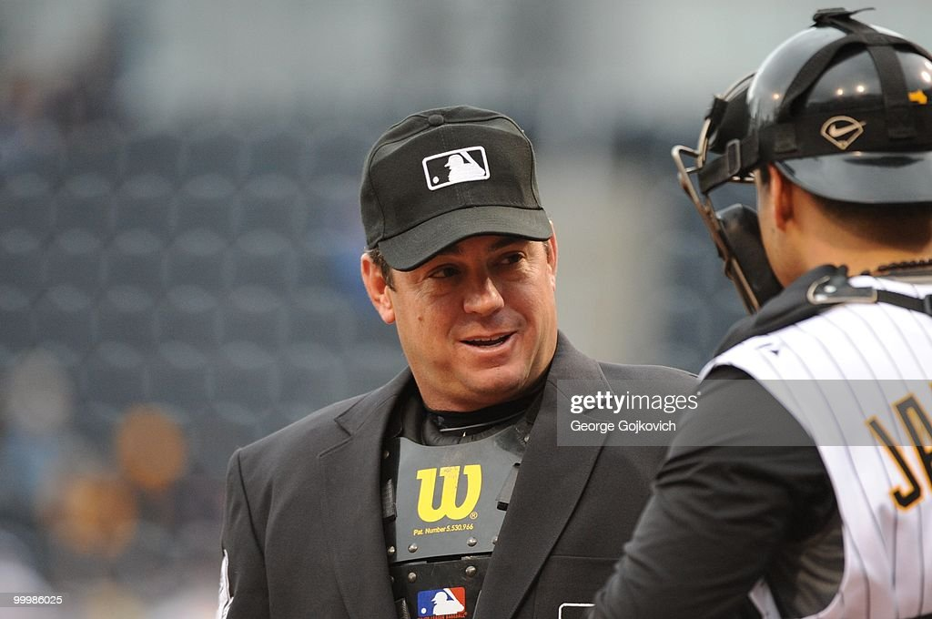 Major League Baseball umpire Rob Drake talks with catcher Jason Jaramillo of the Pittsburgh Pirates during a game against the Cincinnati Reds at PNC...