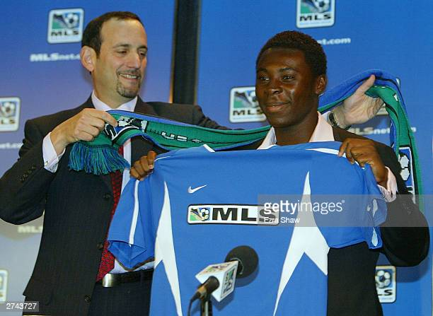 Major League Soccer Commissioner Don Garber gives Freddy Adu a MLS jersey and scarf during a press conference that announce that Adu signed a...