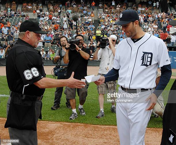 Major League umpire Jim Joyce receives the games lineup card from pitcher Armando Galarraga of the Detroit Tigers before the start of the game...