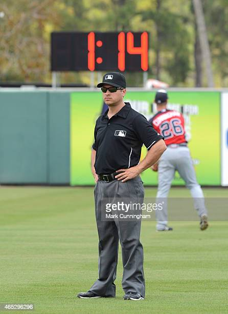 Major League umpire Mark Wegner looks on while the new baseball paceofplay inning break clock is shown in the background during the Spring Training...