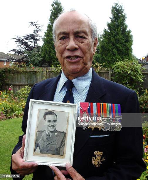 Major Neville Hogan a former Chindit soldier in Burma holding a photo of himself as a young soldier at his home in Hemel Hempstead Hertfordshire...