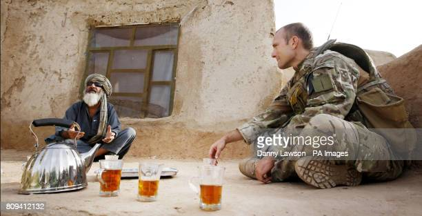 Major Nik Cavill of XRay Company 45 Commando Royal Marines with a local man in the village of Siadabad while on patrol from Patrol Base Kalang in...