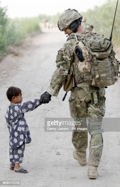 Major Nik Cavill of XRay Company 45 Commando Royal Marines with a local child in the village of Siadabad while on patrol from Patrol Base Kalang in...