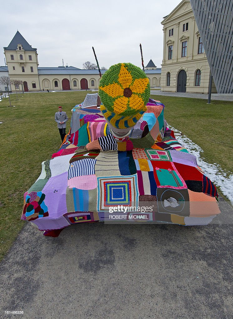 Major of the German Bundeswehr Sebastian Bangert looks at a piece of knitted fabric covering a tank which stands in front of the Museum of Military History in Dresden, eastern Germany, on February 11, 2013. The Leopard I tank takes a stand with a cross-generational handicrafts project against war and violence on the occasion of the 68nd anniversary of the bombing of Dresden.