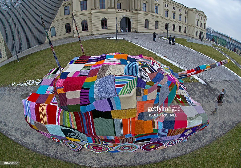 Major of the German Bundeswehr Sebastian Bangert looks at a piece of knitted fabric covering a tank which stands in front of the Museum of Military History in Dresden, eastern Germany, on February 11, 2013. The Leopard I tank takes a stand with a cross-generational handicrafts project against war and violence on the occasion of the 68nd anniversary of the bombing of Dresden. AFP PHOTO / ROBERT MICHAEL