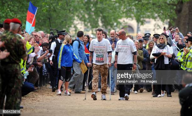 Major Phil Packerleft who lost the use of his legs during an attack in Basra last February accompanied by his friend and 'walking buddy' Martyn Bird...