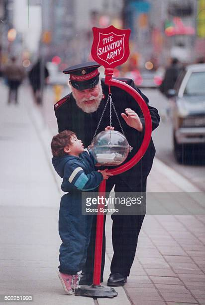 Major Robert MacKenzie helps Leanna Hunt make a donation as the Salvation Army launches its Christmas Kettle Appeal campaign yesterday The Army...