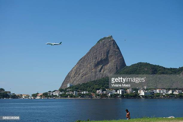 A major tourist attraction Sugar Loaf rises across the Guanabara bay with a plane flying on it's way out of Rio
