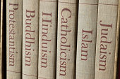 Book spines listing major world religions - Judaism, Islam, Catholicism, Hinduism, Buddhism and Protestantism.