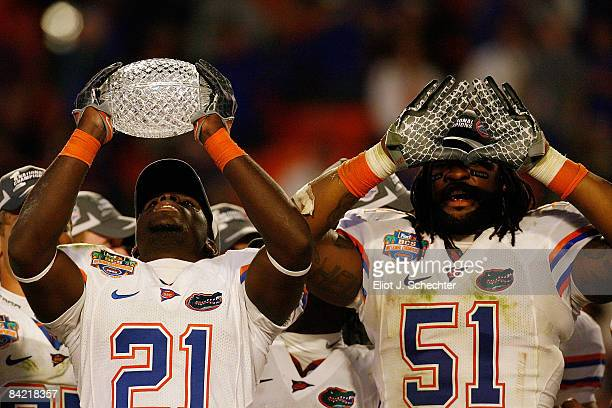 Major Wright and Brandon Spikes of the Florida Gators celebrate with the trophy after defeating the Oklahoma Sooners in the FedEx BCS National...