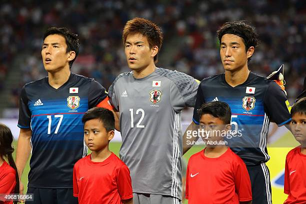 Makato Hasebe Nishikawa Shusaku and Mu Kanazaki of Japan sing the national anthem during the 2018 FIFA World Cup Qualifier match between Singapore...
