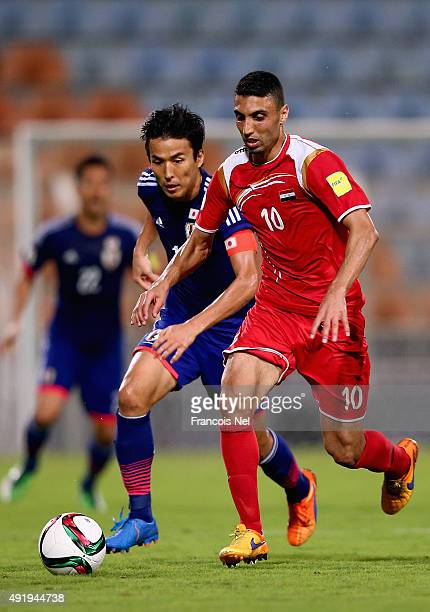 Makato Hasebe of Japan battles for the ball with Abdulrazak Al Hussein of Syria during the 2018 FIFA World Cup Asian Group E qualifying match between...