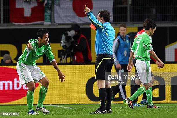 Makato Hasebe of Wolfsburg argues with referee Peter Sippel after he gets the yellow red card during the Bundesliga match between VfL Wolfsburg and...