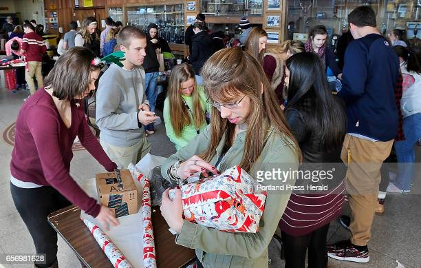 Makayla Goulet right puts a category name sticker on her wrapped gift as Thornton Academy students wrap over 300 presents to give to 12 families...
