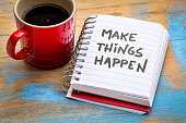 Make things happen motivational reminder or advice - handwriting in a small notebook with a cup of coffee