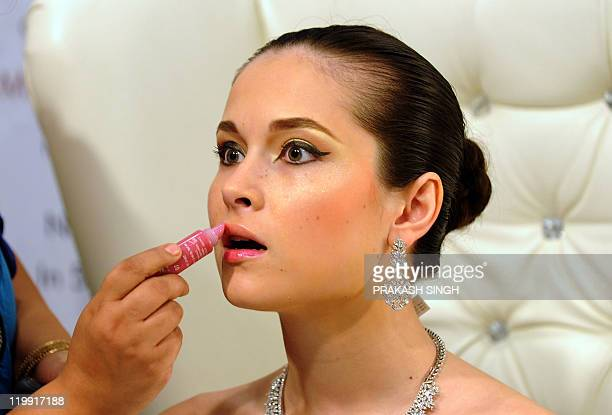 Make up artisit Megha Khanna gives final touches to a model prior to a fashion show during the 'Wedding Asia' exhibition in New Delhi on July 22 2011...