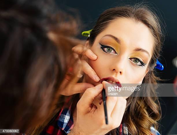 Make up artist applies lipstick on female blue eyed model