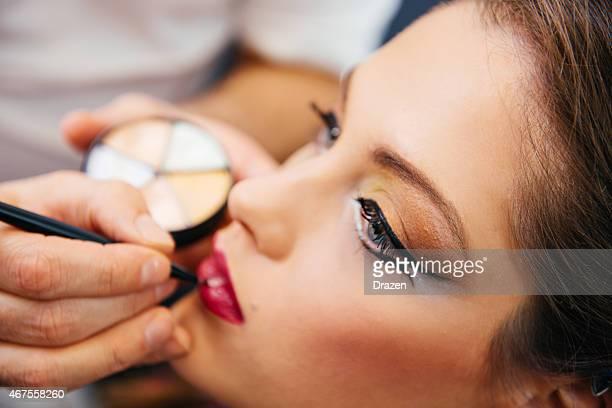 Make up artist applies lipstick on female model