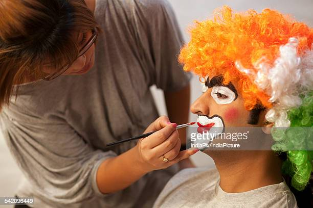 Make up artist applying make up to clown