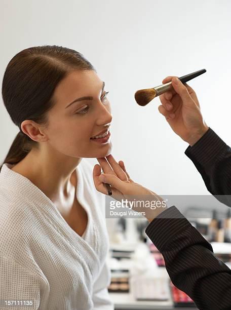 Make up artist applying make up to woman.