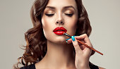 Graceful hands of professional make-up master, with the blue manicure on the nails,  is painting in the red color lips of splendid young woman. Creation of perfect make up in progress. Makeup,manicure